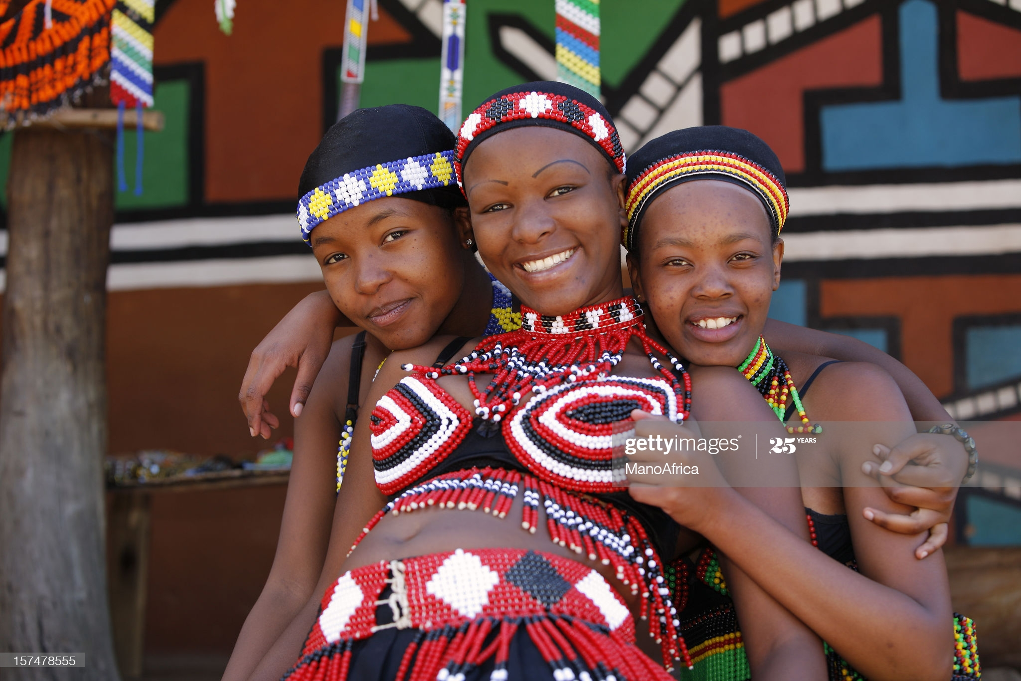 Three young Zulu women friends, dressed in traditional beaded Zulu garments, pose happily for the camera. The Zulu tribe is found mainly in Kwazulu-Natal, South Africa.