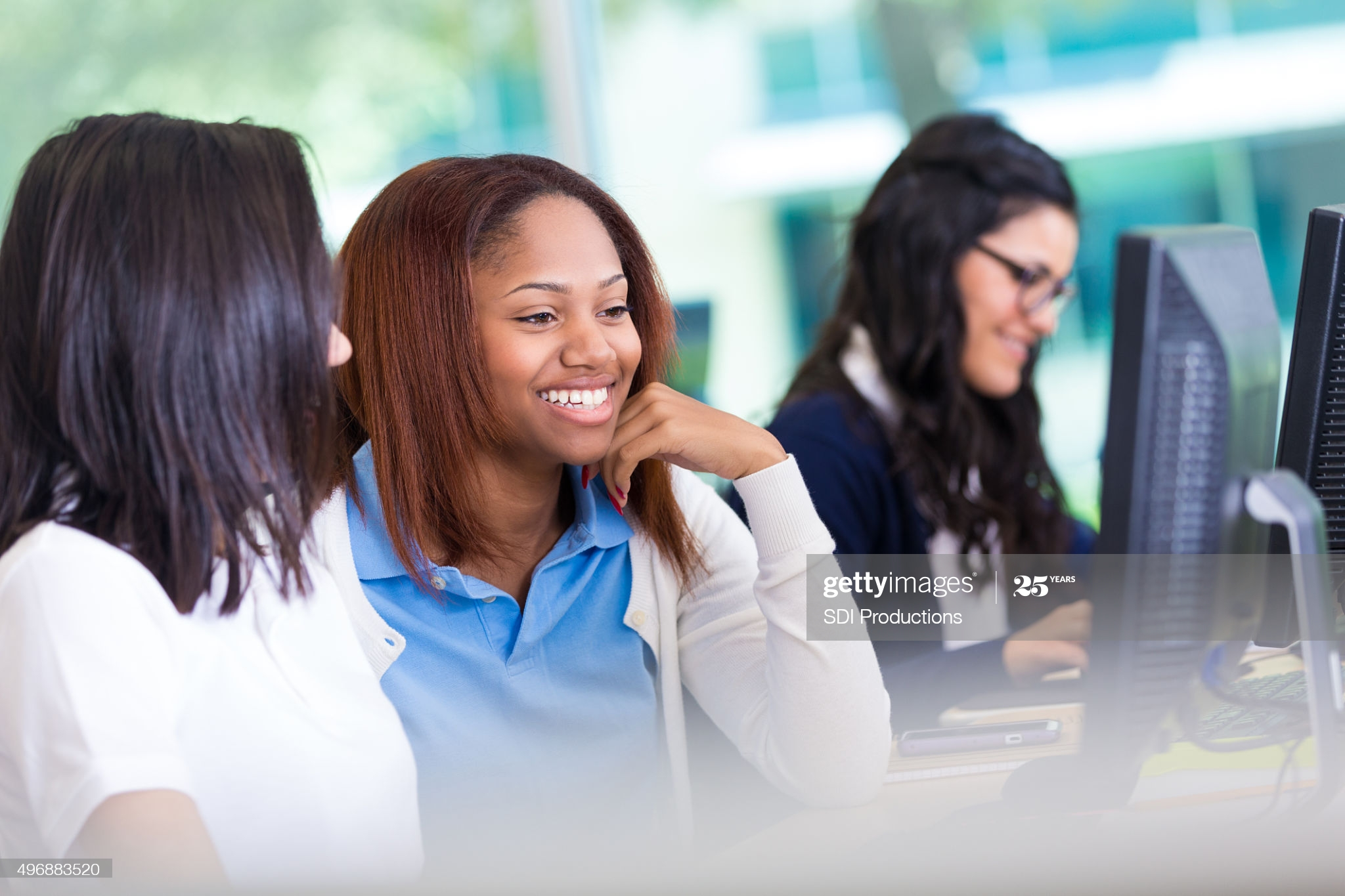 Teenage African American and Hispanic girls are working on assignment together in private high school computer lab classroom. Students are looking at computer monitor and smiling. They are wearing private school uniforms.