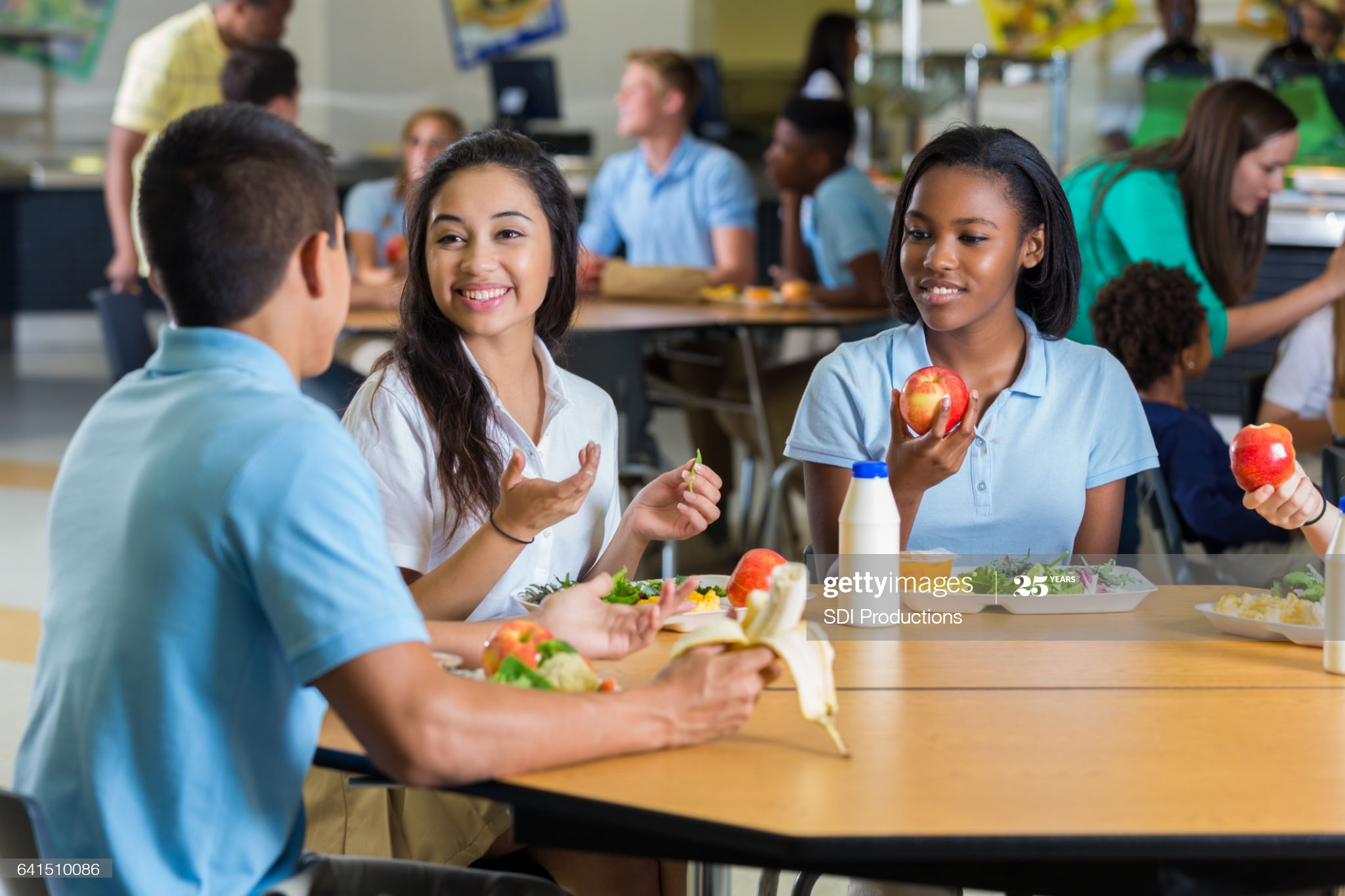 Male and female teenagers enjoy eating lunch together in the school cafeteria. They are wearing school uniforms.