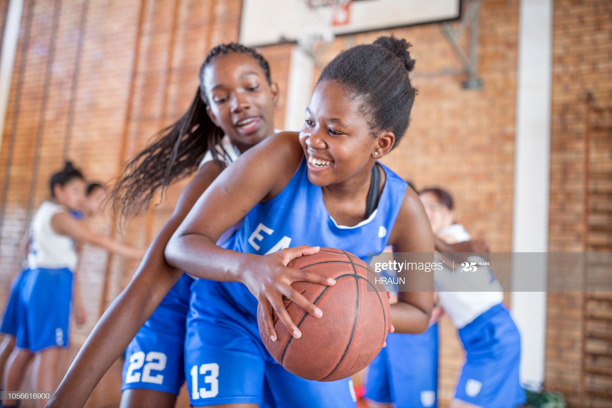 Smiling female defending basketball from opponent. Teenage girls are playing match in court. They are in sports uniform.